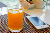 Verre de jus d'orange avec téléphone portable. — Photo