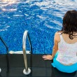 Rear view of a pretty woman sitting on the edge of blue swimming — Stock Photo