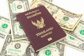Thailand passport on U.S. Currency bank note. — Stock Photo