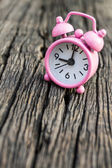 Ssmall pink watch on wood background. — Foto de Stock