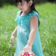 Little Asian girl with basket of flower — Stock Photo