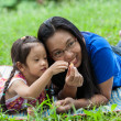 Mother playing and teaching daugther in garden — Stock Photo