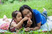 Mother playing and teaching daugther in garden — Stockfoto