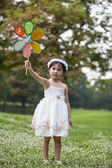 Little cute girl in white dress playing wind wheel toy — Stock Photo
