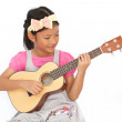Little asian girls sing a song and playing ukulele isolate on wh — Stock Photo #42856981