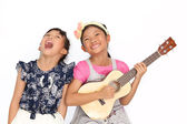 Little asian girls sing a song and playing ukulele isolate on wh — Stock Photo