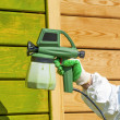 Hand painting wooden wall with spray gun — Stock Photo