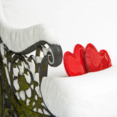 Two red hearts in snow on a garden bench — Stock Photo