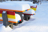 Colored outdoor benches in winter with a lot of snow — Stock Photo
