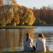 Two women sitting on the shore of Lake — Stock Photo