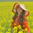 Beautiful woman on blooming rapeseed field — Stock Photo