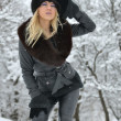 Young woman with black fur in snow — Stock Photo