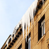 Icicles on the roof of the old house — Stockfoto