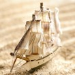 Stock Photo: Wooden sail ship toy model in the sea sand close-up