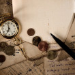 Vintage pocket clock, pen and money on old letters texture — Stock Photo