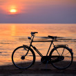 Old vintage bicycle on the beach against sunset in the sea — Stock Photo