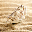 Wooden sail ship toy model in the sea sand close-up — Стоковая фотография