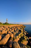 Baltic sea shore with lighthouse at the sunset. Riga, Latvia — Stock Photo