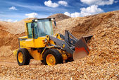 Bulldozer working in sawdust — Stock Photo