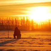 Pescatore in attesa di pesce su ghiaccio presso il sunrise — Foto Stock