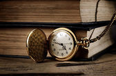 Vintage pocket clock and old books — Stock Photo