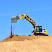 New yellow excavator working on sand dunes — Stock Photo