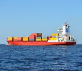 Red containership loaded with colorful cargo containers — Foto de Stock