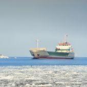 Cargo ship in port med fyr i bakgrunden — Stockfoto