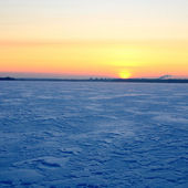 Colorful sunset at the snowy Baltic sea shore — Stock Photo