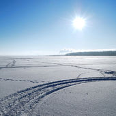 Sun above frozen lake in winter — Stock Photo