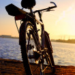 Bicycle silhouette against colorful sunset and industrial port background — Stock Photo
