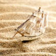 Wooden sail ship toy model in the sea sand close-up — Stock Photo #32832557