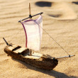 Stock Photo: Wooden sail ship toy model in the sea sand