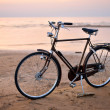 Stock Photo: Old vintage bicycle on beach against seat sunset.