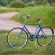 Stock Photo: Old vintage blue bicycle in rural area
