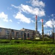 Industrial factory producing electricity with pipes against blue sky — Stock Photo #32838125