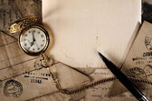Vintage pocket clock and pen on old letters texture — Stock Photo