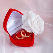 Two wedding rings in red case and a rose — Stock Photo
