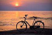 Vieja bicicleta vintage en la playa contra la puesta de sol en el mar — Foto de Stock