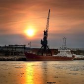 Cargo ship loading in port at the sunrise — Stok fotoğraf