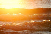 Waves close-up at the sunset with bright halo — Stock Photo
