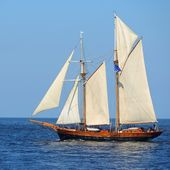 Old historical tall ship (yacht) with white sails in blue sea — Stock Photo