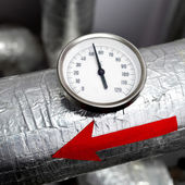 Industrial thermometer red arrow on a water pipeline — Stock Photo