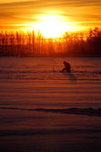 Fisherman waiting for fish on ice at the sunrise — Stock Photo