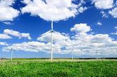 Wind turbines at the meadow against blue sky — 图库照片