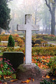 Cross in fog at the cemetary — Stockfoto