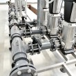 Stock Photo: New shiny pipes and large pumps in industrial boiler room
