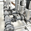 New shiny pipes and large pumps in industrial boiler room — Stock Photo #37436345