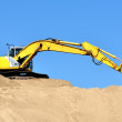 New yellow excavator working on sand dunes — Stock Photo #38697367
