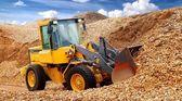 Bulldozer working in sawdust — Stock Photo